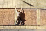Rear view of woman walking on railing of brick wall - CAVF07757