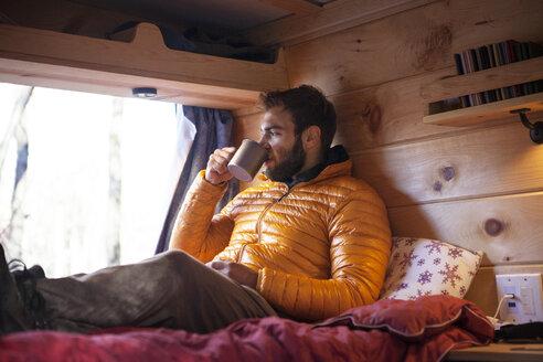 Man having drink while sitting in camper van - CAVF07790
