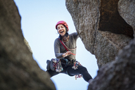 Low angle view of happy woman rock climbing - CAVF07805