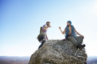 Friends doing fist bump while sitting on rock against clear sky - CAVF07808