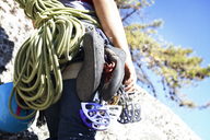 Midsection of woman with climbing equipment standing on rock - CAVF07814