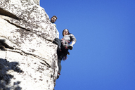 Low angle view of man looking at girlfriend rappelling against clear blue sky - CAVF07820