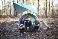 Portrait of friends sitting on fallen tree trunk by tent in forest - CAVF07832