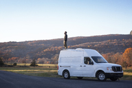 Man standing on camper van against clear sky - CAVF07838
