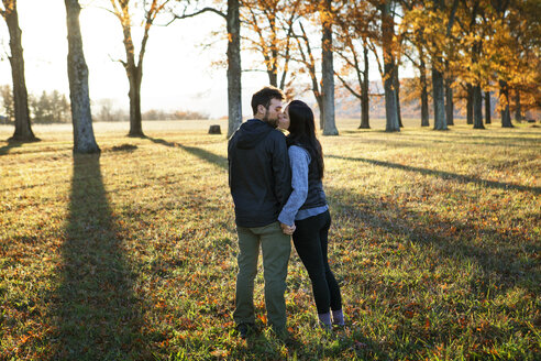Couple kissing while standing on field - CAVF07841