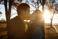 Side view of affectionate couple kissing while standing on field - CAVF07844