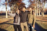 Friends taking selfie while standing on field - CAVF07847