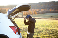 Side view of man wearing headlamp while standing by car on field - CAVF07850