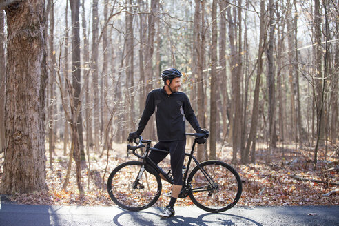 Cyclist standing by bicycle on road at forest - CAVF07859