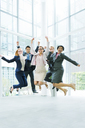 Business people jumping in office building - CAIF15751