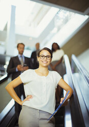 Businesswoman riding escalator in office building - CAIF15754