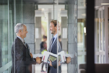 Businessmen shaking hands in office building - CAIF15766