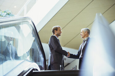 Businessmen shaking hands at top of stairs of office building - CAIF15772