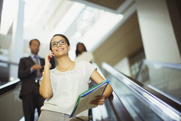 Businesswoman talking on cell phone while going down escalator - CAIF15790