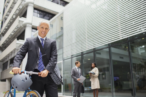Businessman walking bicycle outside of office building - CAIF15796