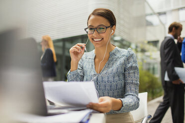 Businesswoman at desk talking on headset - CAIF15799