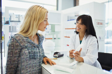 Woman discussing product with pharmacist in drugstore - CAIF15811