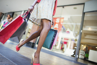 Low angle view of woman carrying shopping bags in shopping mall - CAIF15814