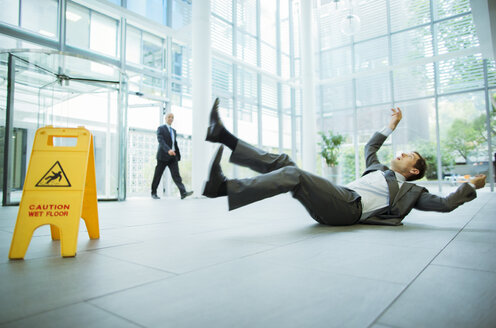 Businessman slipping on floor of office building - CAIF15823