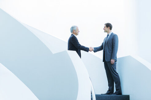 Businessmen shaking hands on staircase of office building - CAIF15826