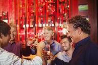 Five smiling men raising toast in bar - CAIF15829