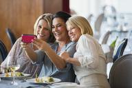Three mature women taking selfie in restaurant - CAIF15865