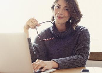 Portrait confident brunette woman holding eyeglasses with laptop - CAIF15883
