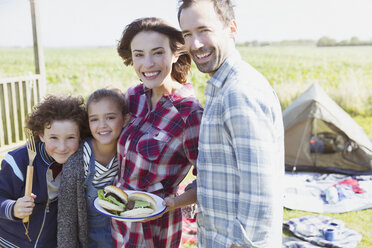 Portrait smiling family with barbecued hamburgers at sunny campsite - CAIF15889