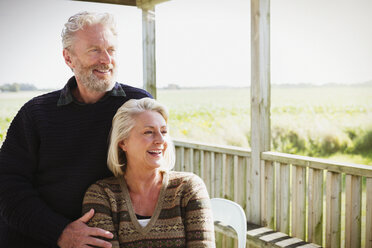 Smiling senior couple looking away on sunny porch - CAIF15895