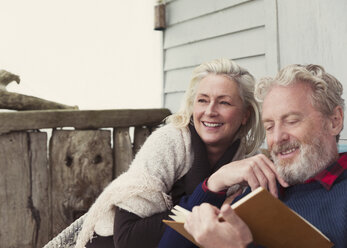 Smiling senior couple reading book on patio - CAIF15904