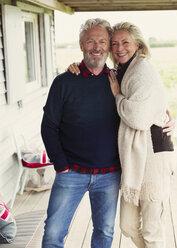Portrait smiling senior couple hugging on porch - CAIF15913