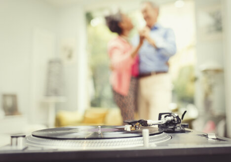 Mature couple dancing in living room behind record player - CAIF15931