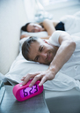 Man in bed turning off morning alarm clock - CAIF15949