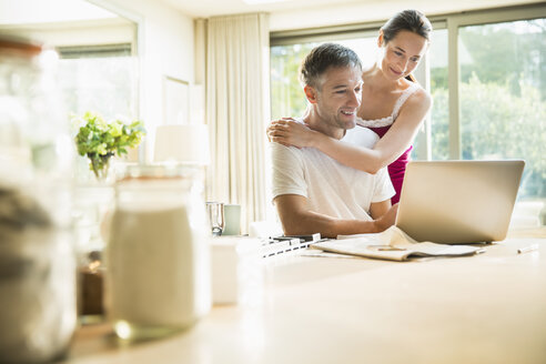 Couple using laptop in morning kitchen - CAIF15961