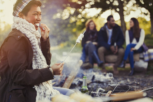 Smiling woman eating roasted marshmallows at campfire - CAIF15997