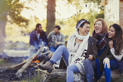 Female friends laughing and roasting marshmallows at campfire - CAIF16003