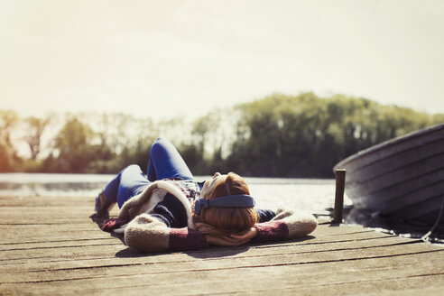Woman relaxing laying on dock listening to music with headphones at sunny lakeside - CAIF16006