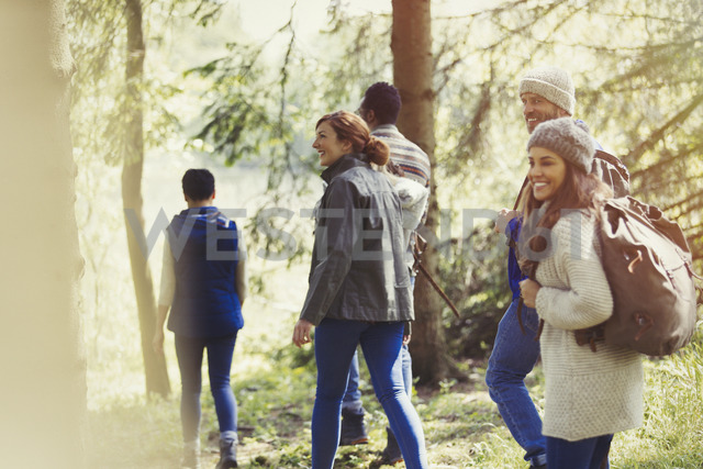 Smiling friends hiking in woods - CAIF16009