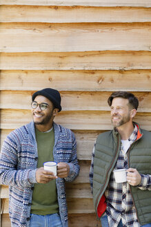 Smiling men drinking coffee outside cabin - CAIF16018