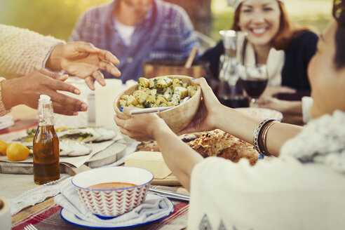 Friends passing food across patio lunch table - CAIF16024