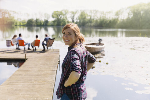Portrait smiling woman at sunny lakeside dock - CAIF16027