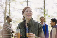 Smiling woman drinking coffee from insulated drink container hiking in woods - CAIF16030