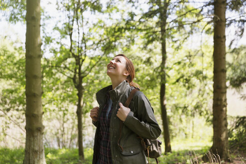 Smiling woman hiking looking up at trees in sunny woods - CAIF16036