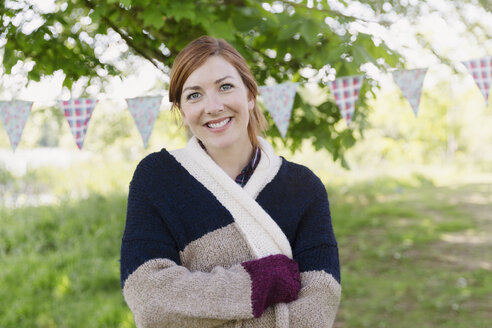 Portrait smiling woman in warm sweater in front of party banner in backyard - CAIF16045