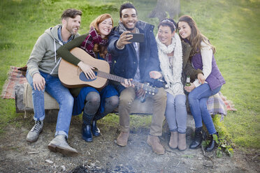 Friends with guitar taking selfie with camera phone at campsite - CAIF16048