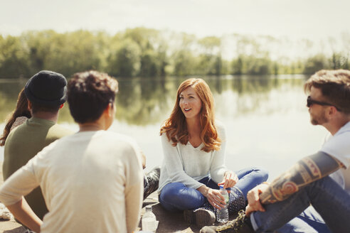 Friends talking at sunny lakeside - CAIF16051