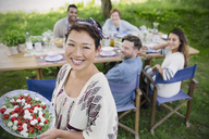 Portrait smiling woman serving Caprese salad to friends at garden party table - CAIF16060