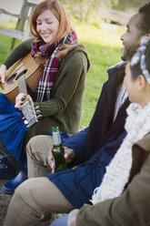 Woman playing guitar with friends drinking beer - CAIF16066