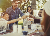 Friends toasting champagne glasses at birthday party patio table - CAIF16084