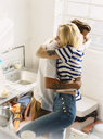 Young couple hugging in apartment kitchen - CAIF16126